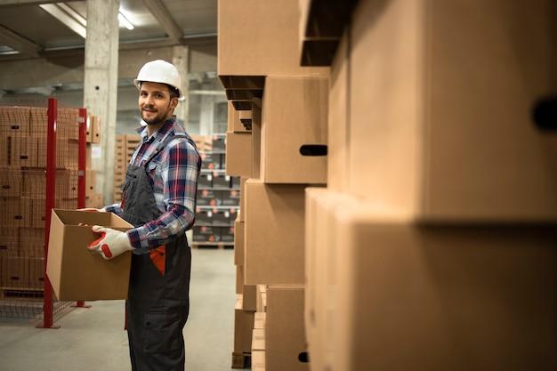 工場の保管場所に商品を移動する段ボール箱を保持している作業服とヘルメットの倉庫作業員の肖像画。