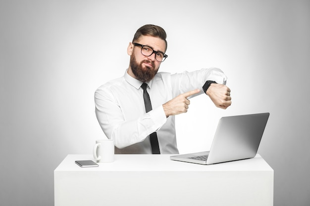 흰 셔츠와 검은색 넥타이를 매고 수염을 기른 잘생긴 젊은 상사의 초상화가 사무실에 앉아서 당신에게 시간이 왔다는 것을 보여주는 손목시계를 가리키고 있습니다. 실내, 스튜디오 촬영, 회색 배경