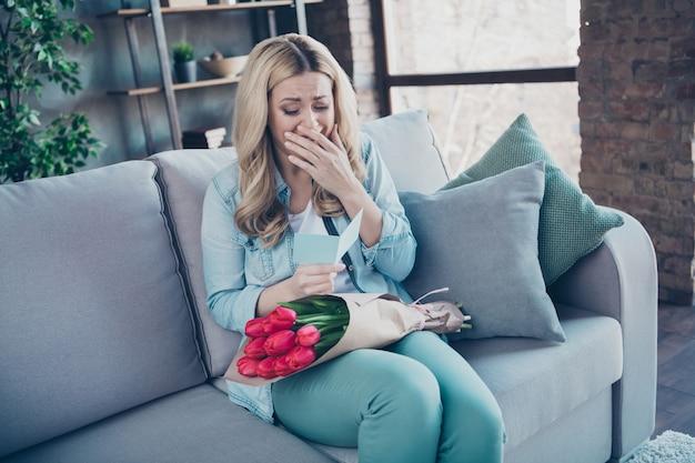 달콤한 카드를 읽고 소파에 앉아 물결 모양의 머리 여자의 초상화 잡고 꽃 울고