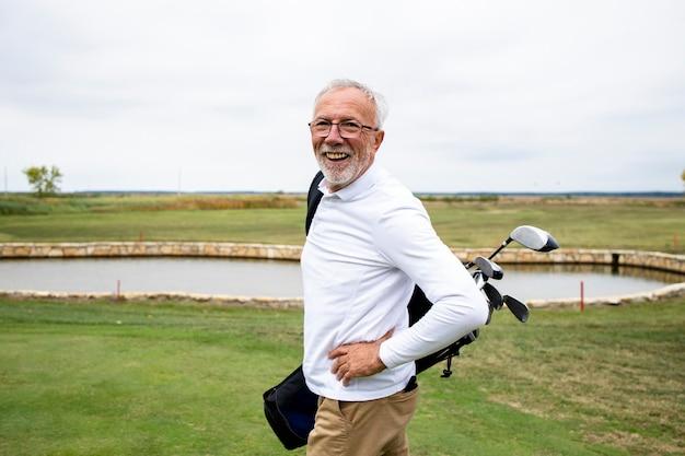 Портрет богатого старшего игрока в гольф с гольф-клубами, наслаждающегося свободным временем на открытом воздухе.