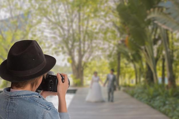 Портрет свадебного фотографа в действии, привлекательная женщина съемки фотографии свадьба