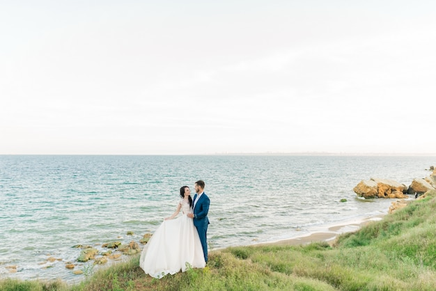 古い大聖堂でポーズをとる花束と結婚式の若い新郎新婦の肖像画。結婚式の日にキスする新婚旅行のカップル、恋に幸せなカップル、結婚式のキス