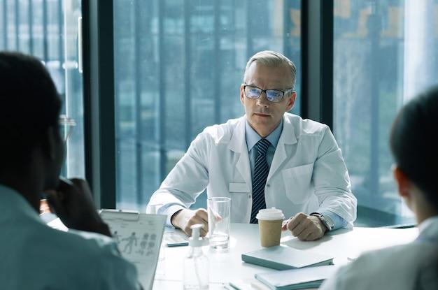 회의실에서 의료 회의를 주재하는 흰색 머리 수석 의사의 초상화, 복사 공간
