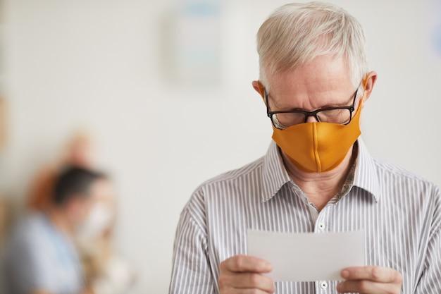 Портрет седого старшего мужчины в маске и чтения рецепта в офисе врачей в медицинской клинике