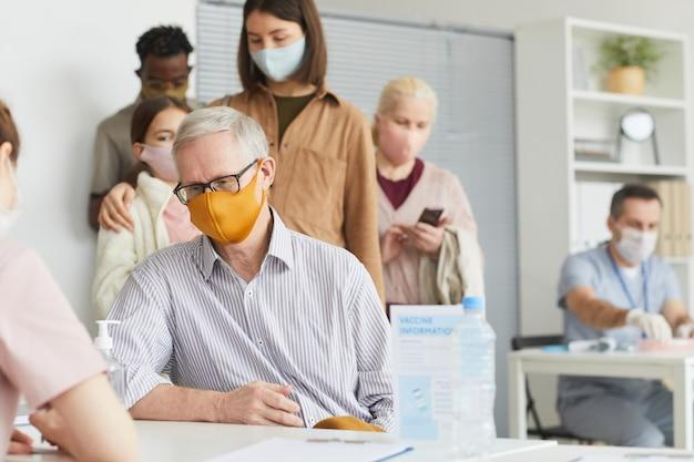 의료 센터에서 코비드 백신에 등록하는 동안 마스크를 쓴 백인 머리 노인의 초상화, 복사 공간