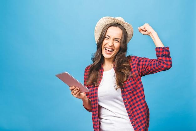 Портрет женщины-победителя взволнован, держа планшетный пк
