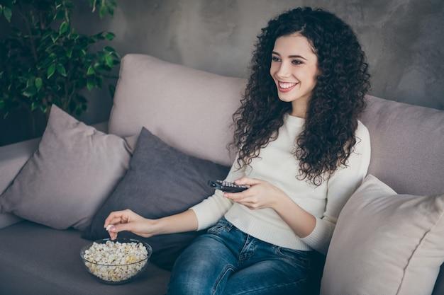 Портрет очаровательной жизнерадостной девушки, сидящей на диване и смотрящей телешоу, отдыхает в современном индустриальном стиле лофта