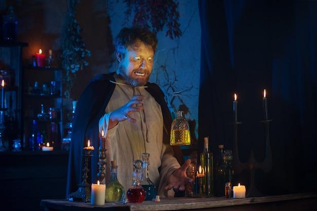 Портрет волшебника с горящими свечами и волшебными зельями