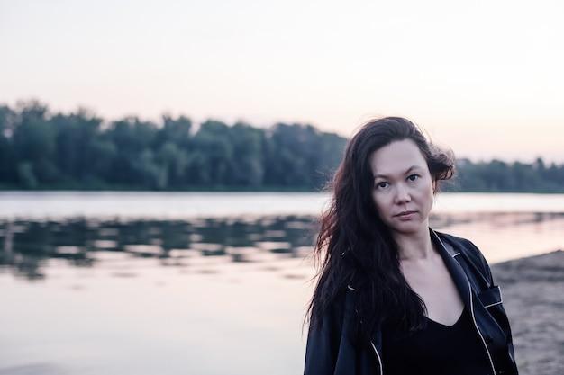 暗いjaのクローズアップで森と池の若い魅力的な女性を背景に女性の肖像画...
