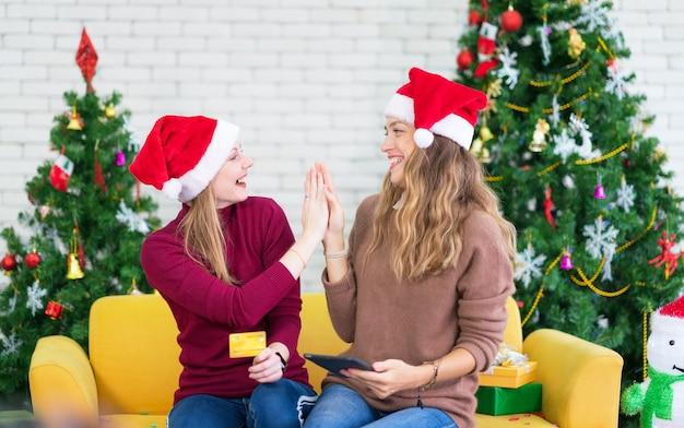 クリスマス休暇、インターネットでのクリスマスと新年の買い物、クレジットカードによる支払いで空白のクレジットカードを示す女性と友人の肖像画。