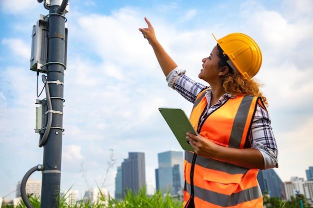 여자 건축가 서 및 사이트에서 확인 태양 전지 패널 극 및 통계 보고서를 위해 태블릿을 사용의 초상화.