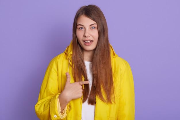 私に話しかけるように頼む女性の肖像画、あなたは私を意味します、カジュアルな黄色のジャケットを着て、ライラックの背景に孤立した彼女の自己を指しているきれいな女性。