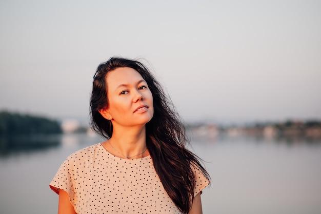若い笑顔のアジアの女性の森のクローズアップ写真を背景に日没時の女性の肖像画...