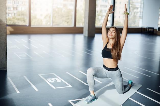 휴식과 요가에 깊은 호흡 여자 선수의 초상화는 빈 아침 체육관 환경에서 포즈. 운동을위한 준비 피트니스 트레이너