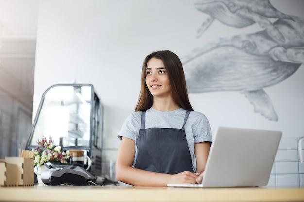 ノートパソコンを使用して日光を楽しんで忙しいカフェで彼女の仕事から少し休んでいる女性バリスタの肖像画。