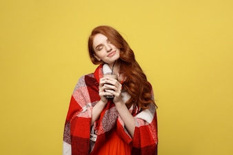Portrait of woman basking with plaid and enjoy drinking chocolate