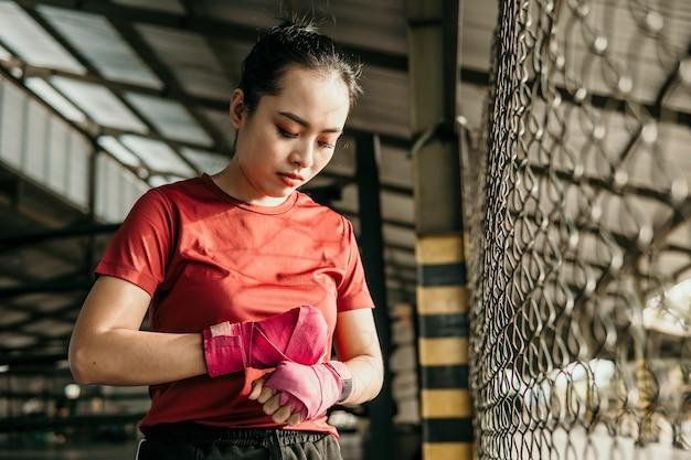 싸움 장소에 손에 속박 테이프를 적용하는 여자 복서 전투기의 초상화