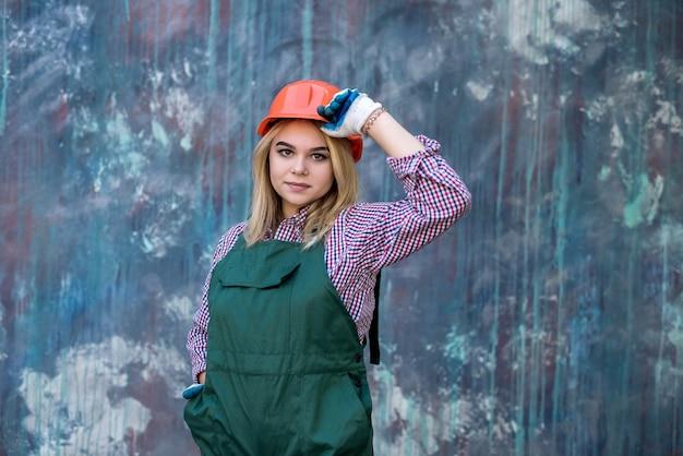 制服とヘルマーを着て立っている女性ビルダー労働者の肖像画。家の改修。