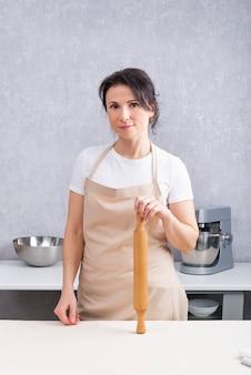 Портрет повара женщины на кухне со скалкой в руках. вертикальная рама.