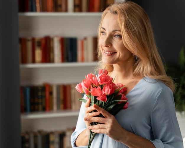 花の花束を保持している女性カウンセラーの肖像画