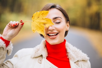 Portrait of woman covering half face with a leaf