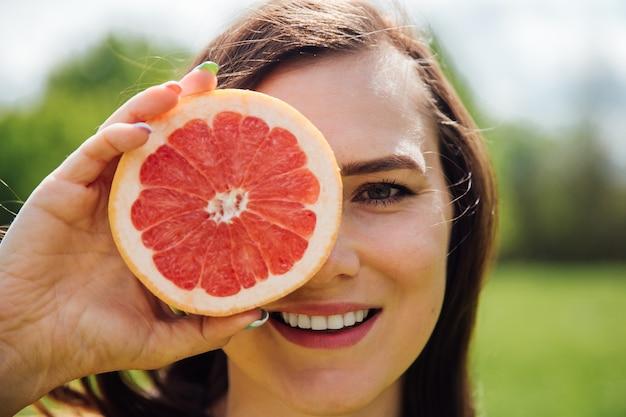 グレープフルーツで目を覆う女性のポートレート
