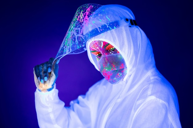Портрет женщины-врача в защитной одежде в ультрафиолетовом неоновом свете