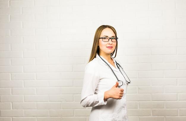 Портрет доктора женщины показывая большие пальцы руки вверх показывать