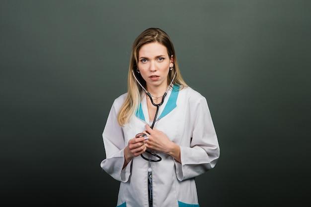 灰色の背景にカメラを見て聴診器で女医の肖像画