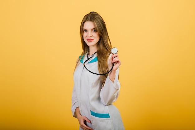 黄色の背景、ヘルスケアにカメラを見て聴診器で女医の肖像画