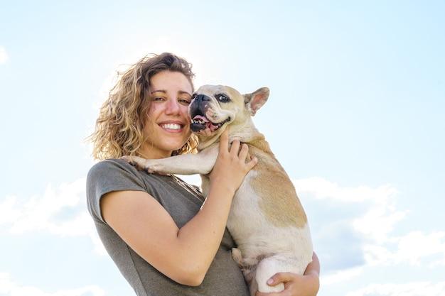 아기 불독을 껴안고 있는 여자 개 애인의 초상화. 애완 동물을 가진 여자의 수평 보기입니다. 야외에서 동물과 함께 하는 라이프 스타일.