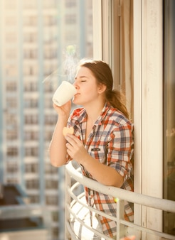 Портрет женщины, пьющей кофе и едящей печенье на балконе