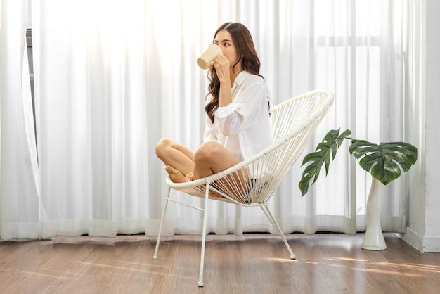 自宅の椅子でコーヒーを飲む女性の肖像画
