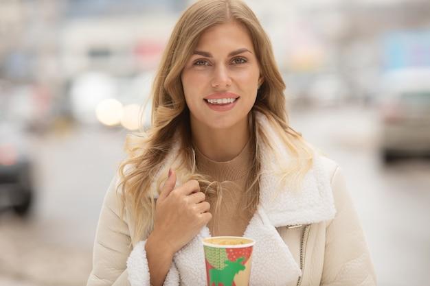 冬の屋外でコーヒーを飲む女性の肖像画。