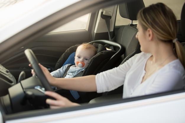 Портрет женщины за рулем автомобиля с ребенком, сидящим на переднем сиденье