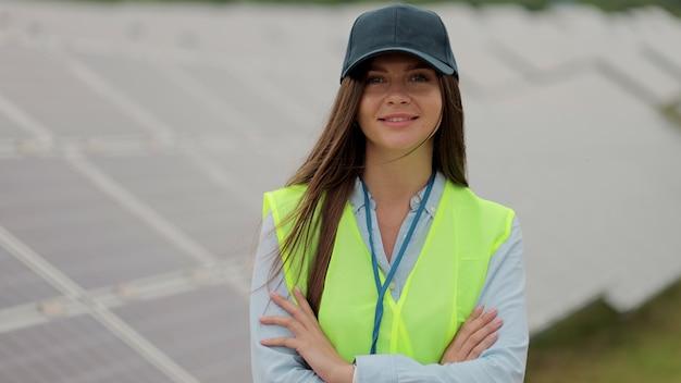 카메라를 보면서 팔을 건너는 여성 엔지니어의 초상화. 태양광 패널 분야. 청정 에너지 생산. 친환경 에너지.
