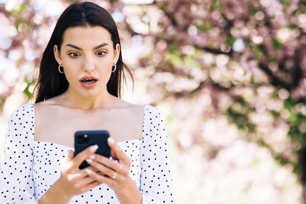 여자의 초상화는 휴대 전화에서 성공을 즐깁니다. 전화로 좋은 소식을 읽는 즐거운 소녀