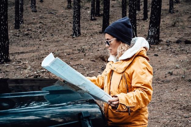 女性の肖像画は車で自然の森の森の旅を楽しむ女性は地図を見る