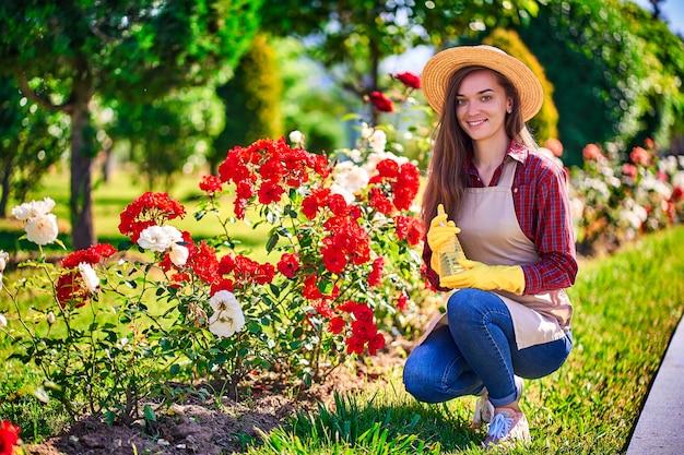 Портрет женщины садовник поливает куст роз