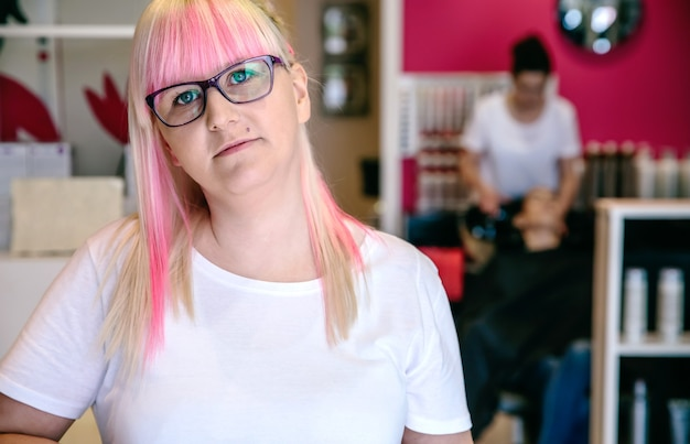 Портрет женщины-парикмахера, стоящей в салоне красоты и волос с сотрудником, моющим волосы женщине на заднем плане