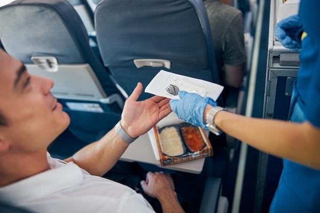 시민 비행기의 잘 생긴 승객을 위해 칼을주는 여자 손의 초상화