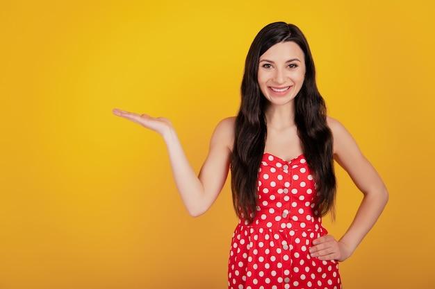 Портрет женщины рука держать пустое пространство носить точечное красное платье на желтом фоне