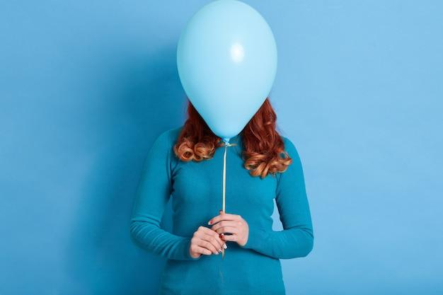女性の肖像画はヘリウム気球の後ろに彼女の顔を隠します