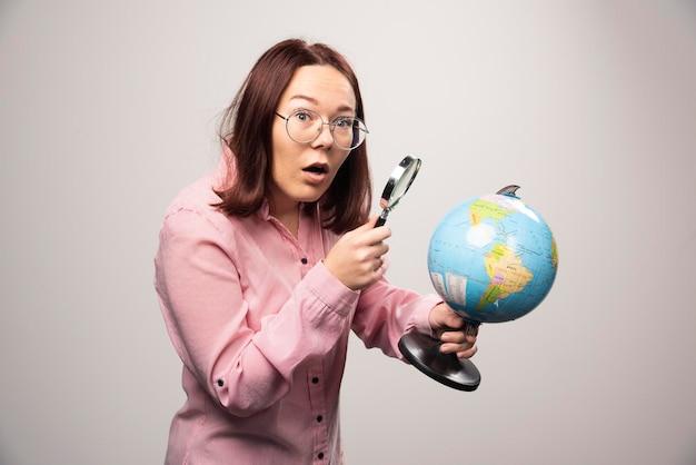 돋보기와 지구 지구를 들고 여자의 초상화. 고품질 사진
