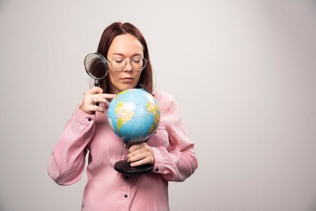 虫眼鏡と地球儀を持つ女性のポートレート。高品質の写真