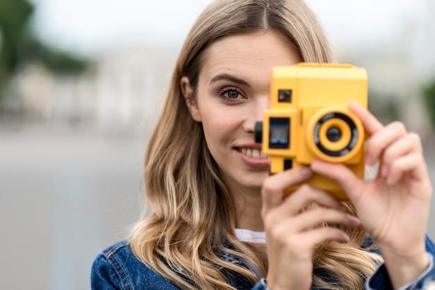 Портрет женщины, держащей ретро желтый фотоаппарат