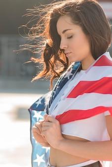 Портрет женщины, держащей большой флаг сша с закрытыми глазами