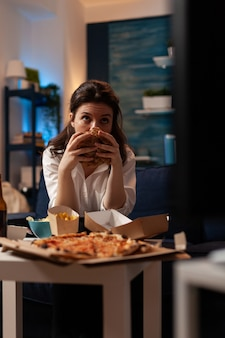 테이크아웃 배달 음식을 먹는 맛있는 버거를 들고 있는 여성의 초상화