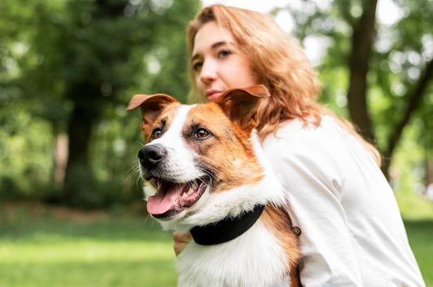Портрет женщины, держащей ее собаку в парке