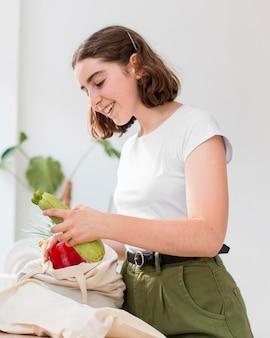 Портрет женщины, держащей органические овощи